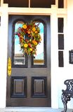Eye-Catching Door With Brightly Colored Flower Wreath Beckons Visitors stock image