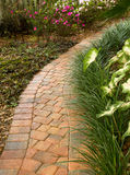 Enticing curved garden path. Curved garden path winds around a beautiful garden royalty free stock image