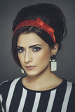 Enticing woman portrait in retro style outfit. Portrait of an elegant enticing fashion female model wearing retro black-and-white stripped blouse, red headband royalty free stock photo