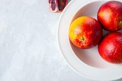 Entier mûr frais et tranches d'oranges sanguines dans un plat sur un whi photo stock