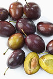 Entire and sliced plums, elevated view Royalty Free Stock Photo