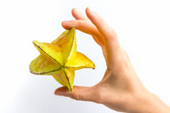 Entire Starfruit in Hand. A carambola, commonly known as starfruit, held on its side, in the hand of a young woman, isolated on white Royalty Free Stock Photos