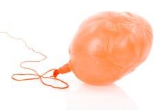 Entlüfteter gelber Ballon an einem Seil; über Weiß Lizenzfreie Stockfotografie