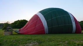 Entlüfteter Heißluftballon mit Korb auf einem Gebiet stockfotos