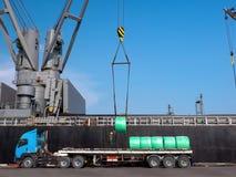 Entladung von Stahlerzeugnissen durch Schiffskran stockbild