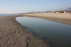 Entlang der Versilia-Küste in Toskana, auf der Promenade entlang dem Sand, treffen Sie häufig Wasserbecken nach dem Sturm, Recht  stockfotografie
