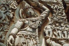 Entlastung mit Lord Krishna, der Mt anhebt Govardhan Grafik des des 12. Jahrhunderts aufwändigen Hoysaleshwara-Steintempels in In Lizenzfreie Stockfotos