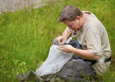 Entomologist in the field. Entomologist collecting bugs from the net with an entomological aspirator in summer Stock Image