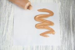 Entone la muestra cosmética poner crema del tubo de fundación líquida Fotografía de archivo