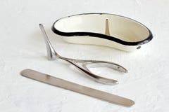 Entonnoir d'oreille dans le bain en forme de rein en métal, spatule en métal, miroir de nez de Vienne sur le fond concret blanc r image stock