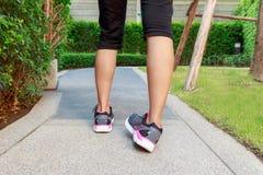 Entorse sportive de cheville de femme tout en pulsant ou courant au parc Photographie stock