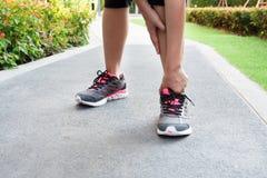 Entorse sportive de cheville de femme tout en pulsant ou courant au parc Photographie stock libre de droits