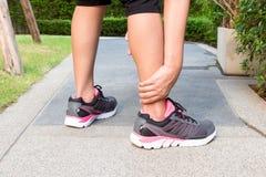 Entorse sportive de cheville de femme tout en pulsant ou courant au parc Photos libres de droits