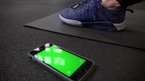Entourer autour de la vue du smartphone avec l'écran de vert de chromakey se trouvant près des espadrilles sur le karrimat dans l banque de vidéos