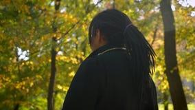 Entourer autour de la vue du type afro-américain avec des dreadlocks marchant et observant la beauté du parc automnal clips vidéos