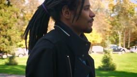 Entourer autour de la vue en gros plan de du jeune type afro-américain avec des dreadlocks marchant sur le fond automnal de parc clips vidéos