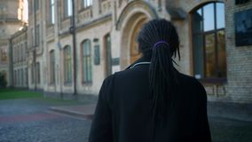 Entourer autour de la vue en gros plan de l'étudiant afro-américain avec des dreadlocks passant par le parc automnal à l'universi clips vidéos