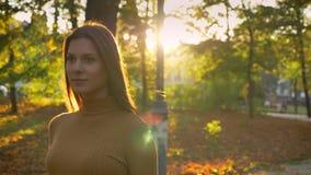 Entourer autour de la vue de la jolie jeune dame marchant autour du parc automnal attrapant la lumière du soleil banque de vidéos