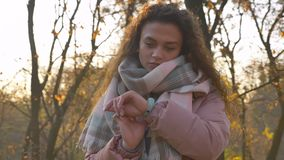 Entourer autour du portrait de la femme aux cheveux bouclés caucasienne regardant la montre sur le fond automnal de parc banque de vidéos