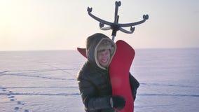Entourer autour du tir du sportif dans le manteau chaud et le capot s'inquiétant une chaise rouge sur son épaule sur le fond de c banque de vidéos