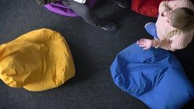 Entourer autour du topshot de l'homme travaillant avec l'ordinateur portable se reposant sur le sac multicolore et la femme march clips vidéos