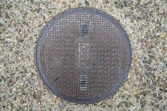 Entourez l'égout en acier de couverture ou en métal de trou d'homme sur la rue au Japon Images stock