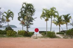 Entrée à la plage blanche de sable avec le signe rouge vide Vue de parc et de mer avec des palmiers Photographie stock