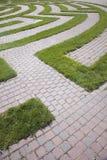 Entrée à un labyrinthe de pavé rond et d'herbe Images libres de droits