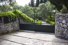 Entrée d'allée à déchenchements périodiques haut par fer d'une villa Paysage architectural de jardin entourant la voie limitée Pi images libres de droits