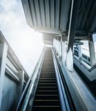 Entrée d'escalator à la station de métro avec la lumière du soleil Futurs concepts photo stock
