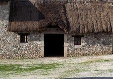 Entrée d'un vieux bâtiment en pierre rural avec le toit couvert de chaume Image libre de droits