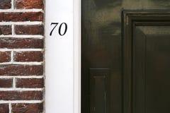 Entrée de bâtiment avec le mur de briques et le numéro de maison foncés à Amsterdam Image libre de droits
