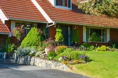 Entrée de maison de famille avec le toit carrelé et la cour délicatement aménagée en parc photographie stock