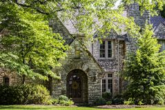Entrée de maison multi-à pignon classieuse de roche avec le porche arqué et entrée principale avec la guirlande et le feuillage l photo libre de droits