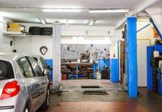 Entrée de service de garage avec les outils, l'ascenseur et la voiture images stock