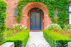 Entrée principale d'un cottage anglais décoré des plantes et des fleurs de jardin photos stock