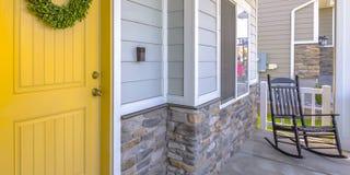 Entrée principale et porche jaunes avec une chaise de basculage photographie stock