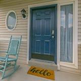 Entrée principale verte d'une maison avec la natte jaune image libre de droits