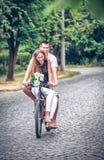 Entraînement d'une jeune paire par la rue de bicyclette vers le bas Photo libre de droits
