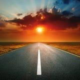 Entraînement sur une route vide contre le coucher de soleil Image libre de droits