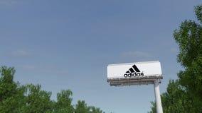 Entraînement vers le panneau d'affichage de publicité avec l'inscription et le logo d'Adidas Rendu 3D éditorial Photos libres de droits
