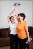 Entraîneur aidant l'exercice aîné de femme Photos stock