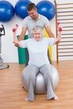 Entraîneur aidant la femme supérieure à soulever des haltères sur la boule d'exercice Image stock