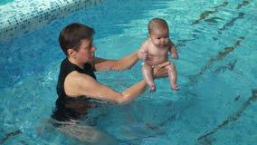 Entraîneur avec le bébé dans la piscine banque de vidéos