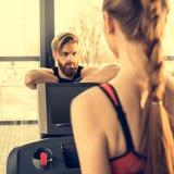 Entraîneur barbu d'homme regardant la femme sportive s'exerçant sur le tapis roulant Image libre de droits