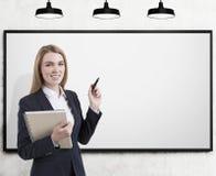 Entraîneur blond d'affaires avec le marqueur, tableau blanc vide images libres de droits