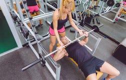 Entraîneur de femme aidant à équiper dans la formation de banc à presse photographie stock