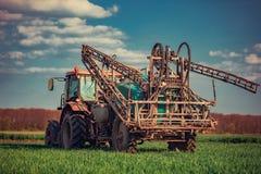 Entraîneur de ferme labourant et pulvérisant sur la zone Image libre de droits