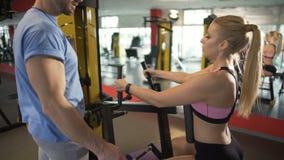 Entraîneur de forme physique donnant des conseils à son client féminin, enseignant comment faire l'exercice clips vidéos