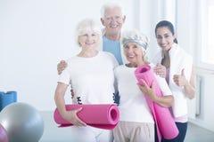 Entraîneur de forme physique félicitant les personnes âgées Image libre de droits